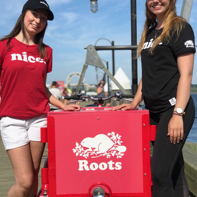 Two roots canada representitves pose with an Icicle Tricycles branded Ice Cream outdoor advertising Bike in Toronto