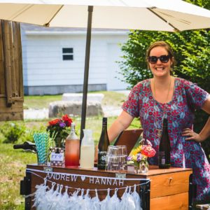 Woman smiles in Halifax under a patio umbrella connected to a cedar box ice cream bike furnished as a wedding bar