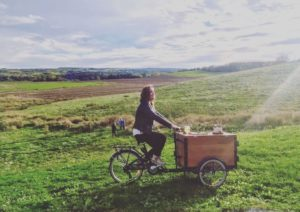 woman riding a custom stained cedar ice cream bike in the fields of Halifax on a sunny day
