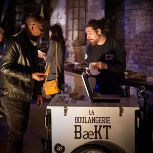 A vendor sells baked goods to a customer from a commercial cargo vending bike at a popup artist event in Montreal Quebec