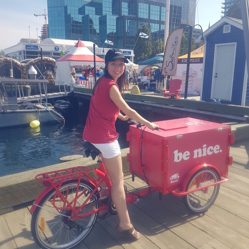 woman smiling while riding a Roots Canada Icicle Tricycle Ice Cream Bike on the Halifax Pier