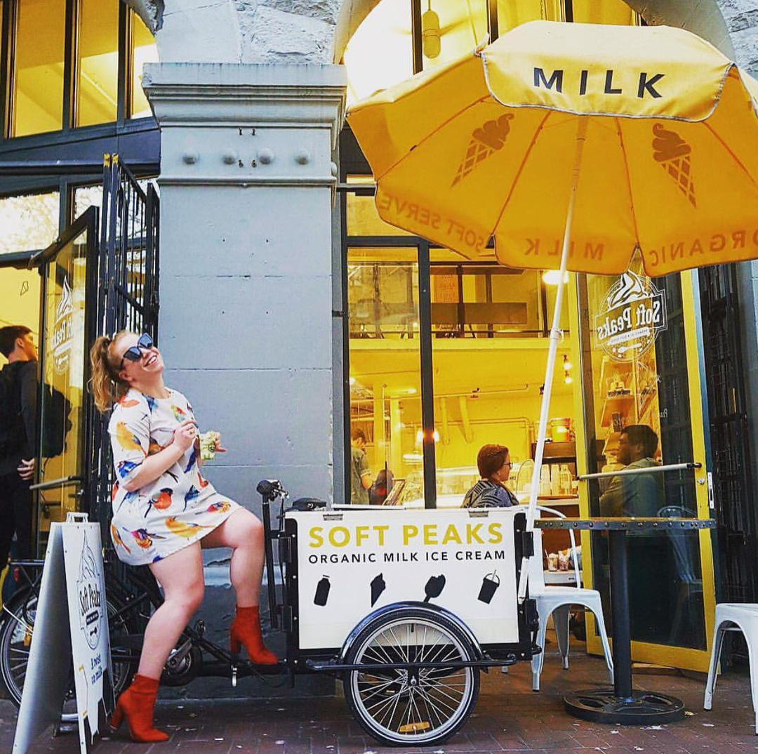 Girl enjoying treat sitting on Soft Peaks Ice Cream Bike with umbrella out front of Ice Cream shop in Vancouver British Columbia