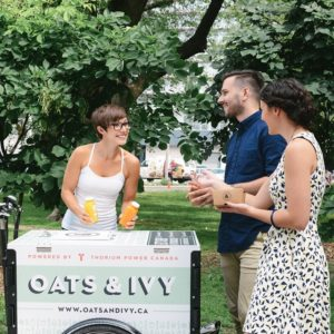 A vendor is selling juice to a couple from an Oats & Ivy branded commercial cargo vending bike in a park in Toronto Ontario