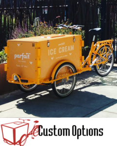 "Icicle Tricycle Parfait branded custom Ice cream bike in parked on the side walk and the Icicle Tricycle logo with text ""Vending Bikes"" adjacent"