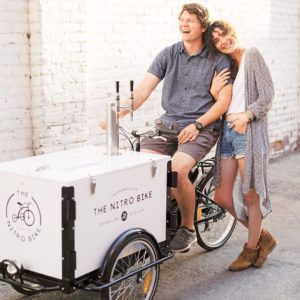 a couple posing with the nitro bike cold brew coffee bike in an alley way